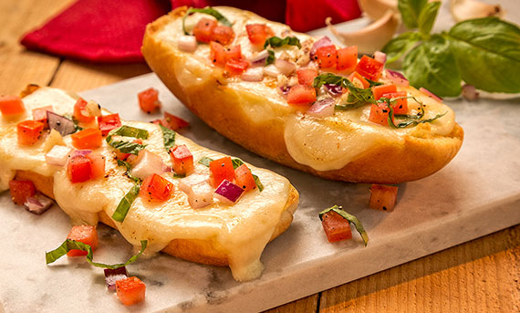 A photo of Ball Park Bun's Easy Cheesy Garlic Bread, with tomatoes, red onions and basil